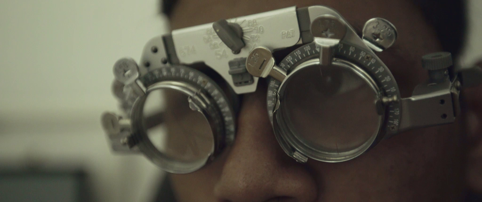 Blind footballer Asri is wearing a testing device with large lenses in a medical examination room.