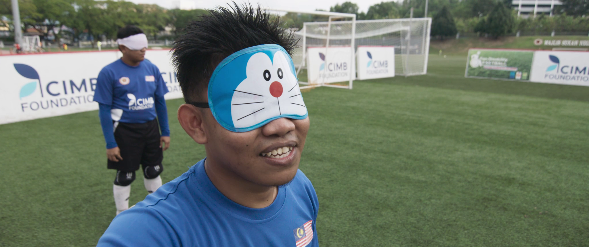 Footballer Kenchot is wearing a cartoon eye mask of a cat's face.