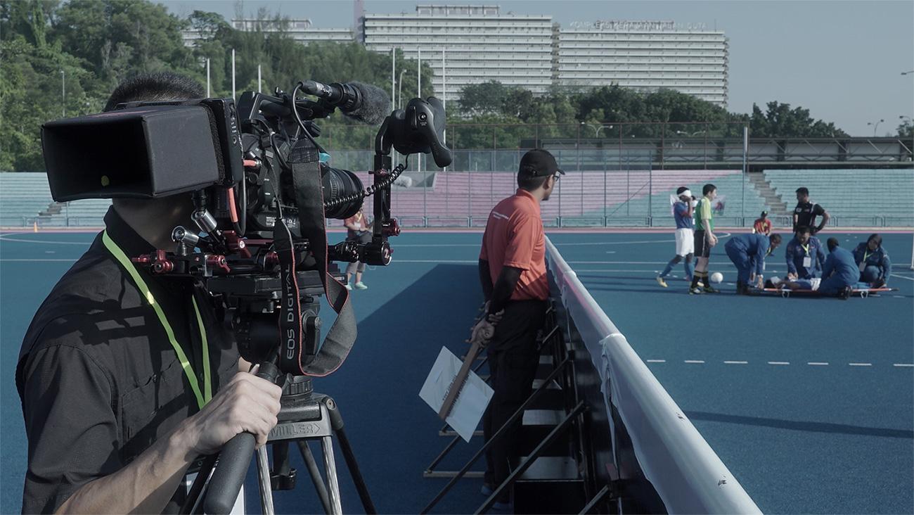 Juru sinematografri Chin Hor merakam pasukan medik memberi bantuan kepada pemain yang tercedera di atas padang semasa IBSA Blind Football Asian Championships.