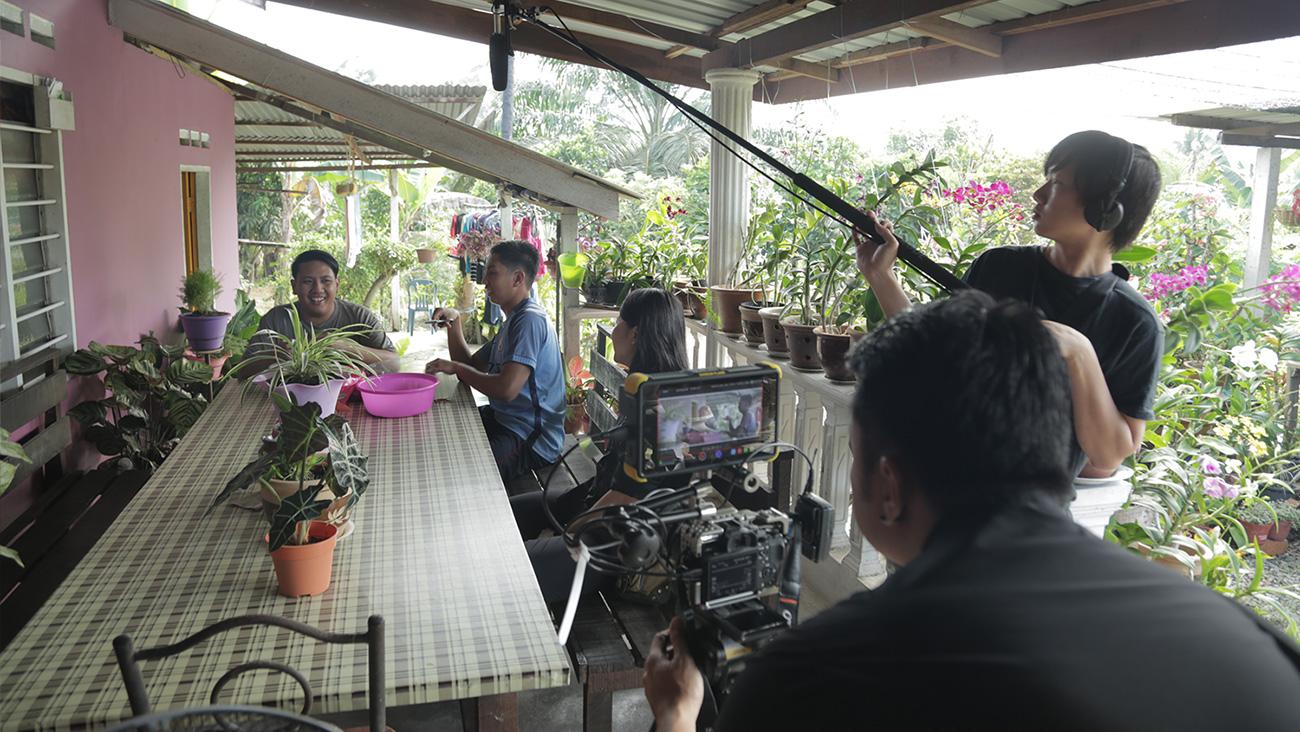 Krew kamera merakam pemain bola sepak Asri bersama adiknya di berada rumah keluarganya.
