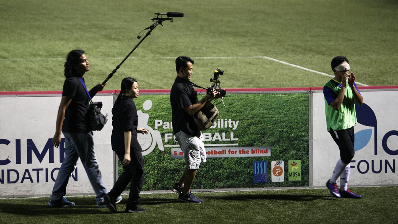 Krew kamera mengekori pemain bola sepak buta Asri di atas padang apabila dia menyeru rakan sepasukannya.