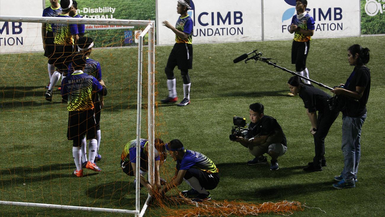 Krew camera merakam dua orang pemain bola sepak memasang jaring ke tiang gol.