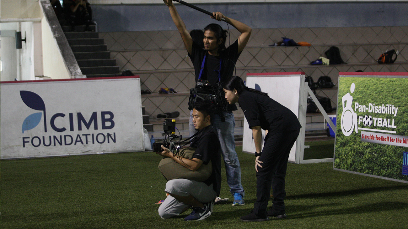Pengarah Wen melihat monitor video di belakang juru sinematografi Chin Hor dan penata audio Izzat sewaktu di atas padang.