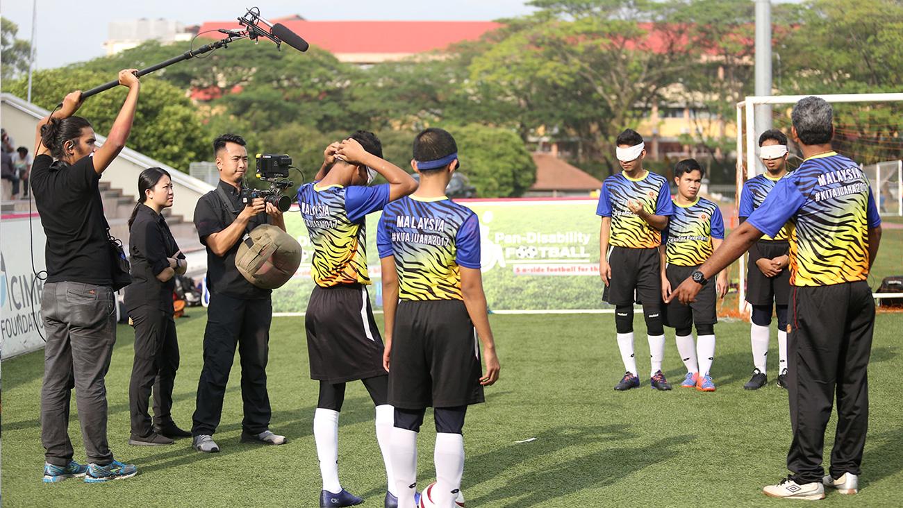 Krew kamera merakam jurulatih Sunny memberi arahan kepada pasukan bola sepaknya ketika sesi latihan di atas padang.