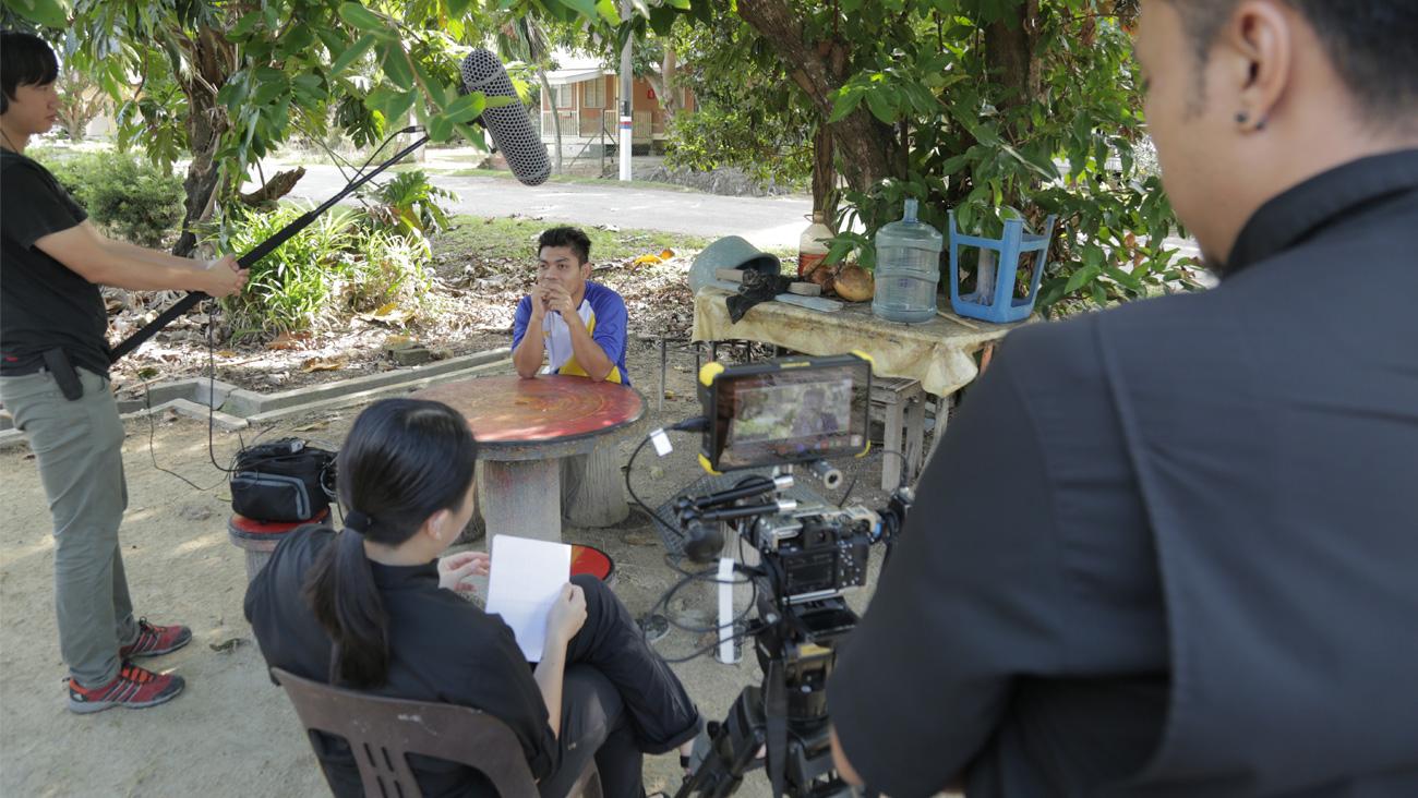 Krew kamera merakam pemain bola sepak Kenchot di luar rumah kampungnya.